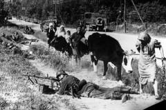 1941. Беженцы проходят мимо немецкого пулеметчика