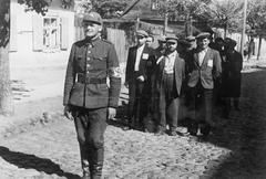 Литовский полицай ведет евреев по вильнюсскому гетто. Июль 1941 года.